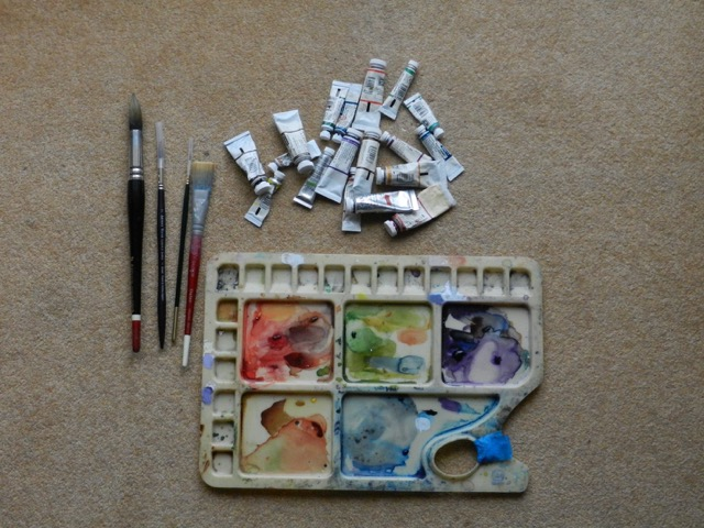 Image of a watercolour pallet, brushes and tubes of paint.